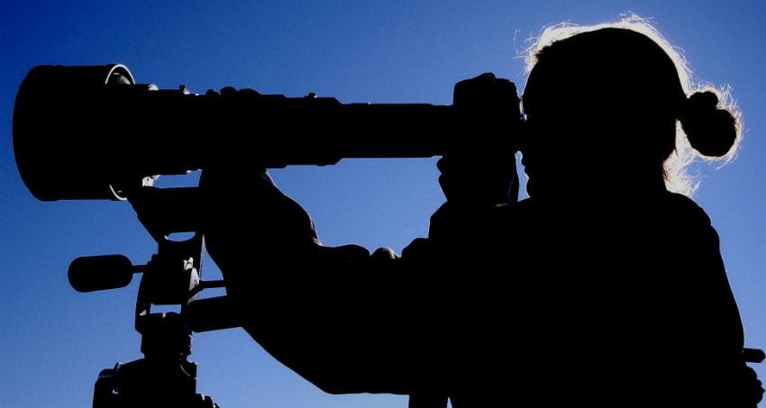 Photographer looking through telescope
